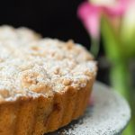 Vertical Image of Blueberry Crumb Cake with pink calla lilies in the background.