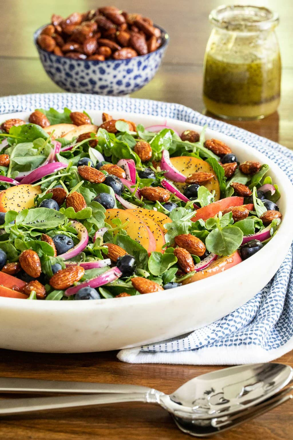Vertical photo of a Blueberry Peach Poppy Seed Salad in a white marble serving bowl with dressing and Sweet and Smokey Candied Almonds in the background.