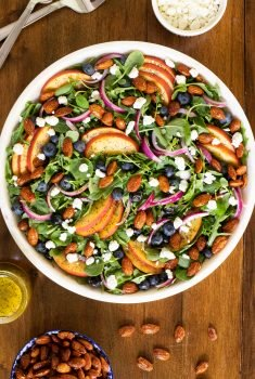 Overhead vertical picture of blueberry peach poppy seed salad on a wooden table