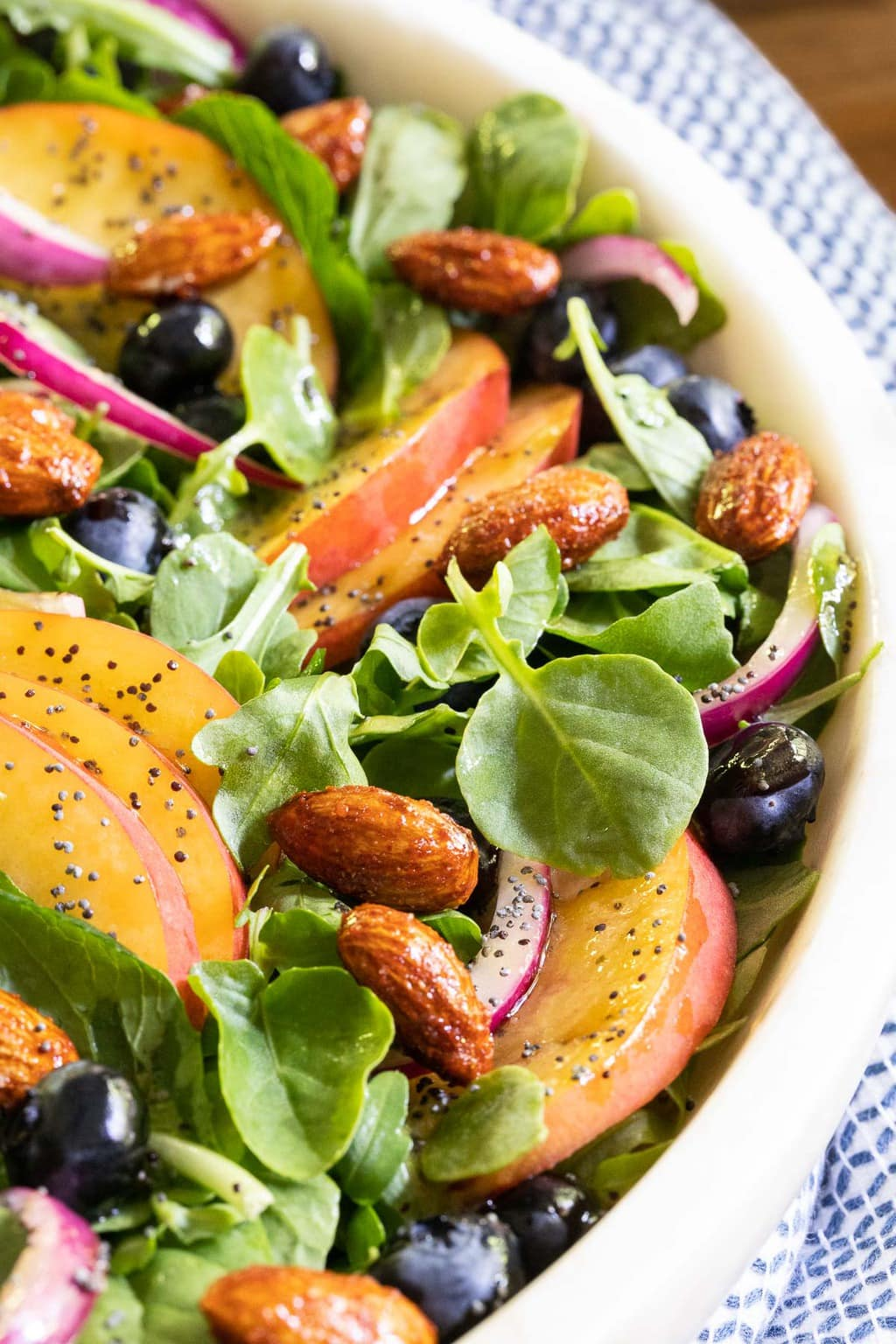 Vertical closeup photo of a Blueberry Peach Poppy Seed Salad in a white marble serving bowl.