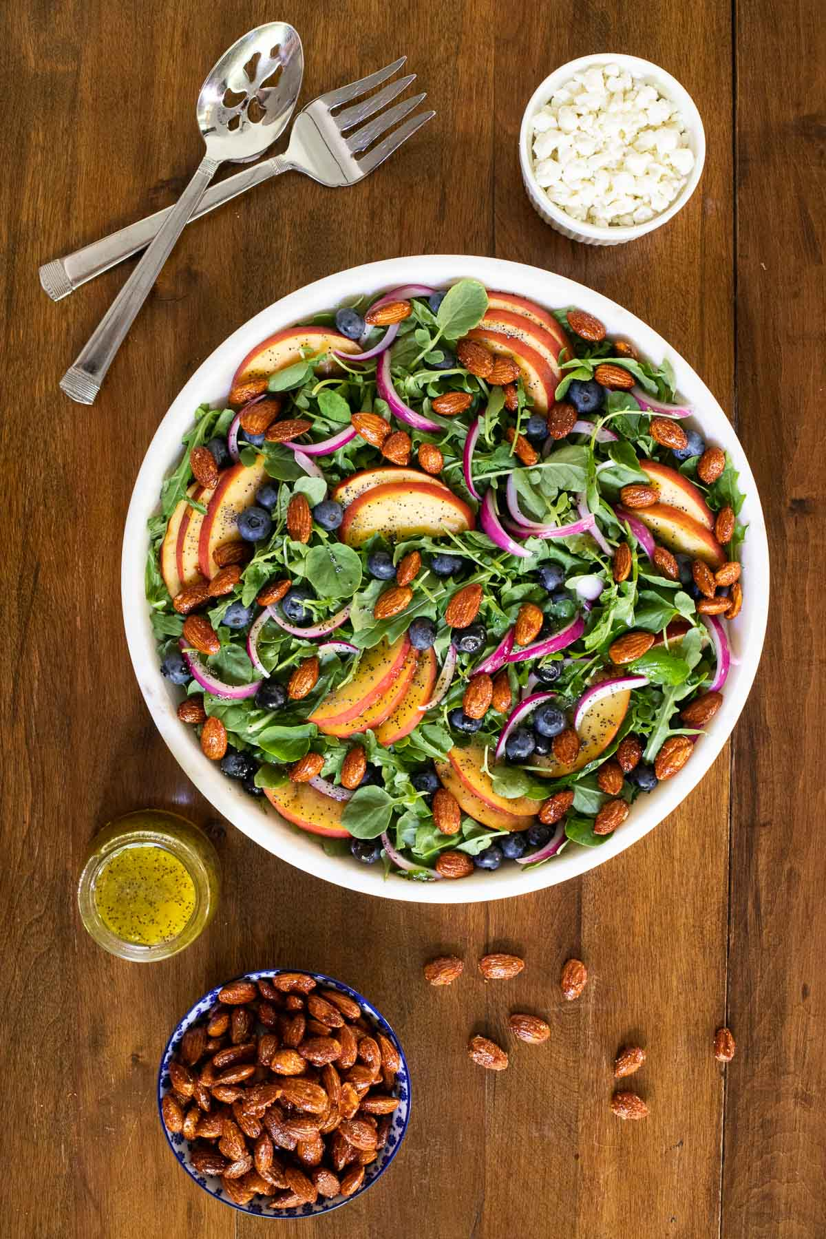 Overhead vertical photo of a Blueberry Peach Poppy Seed Salad in a white marble serving dish on a wood table.