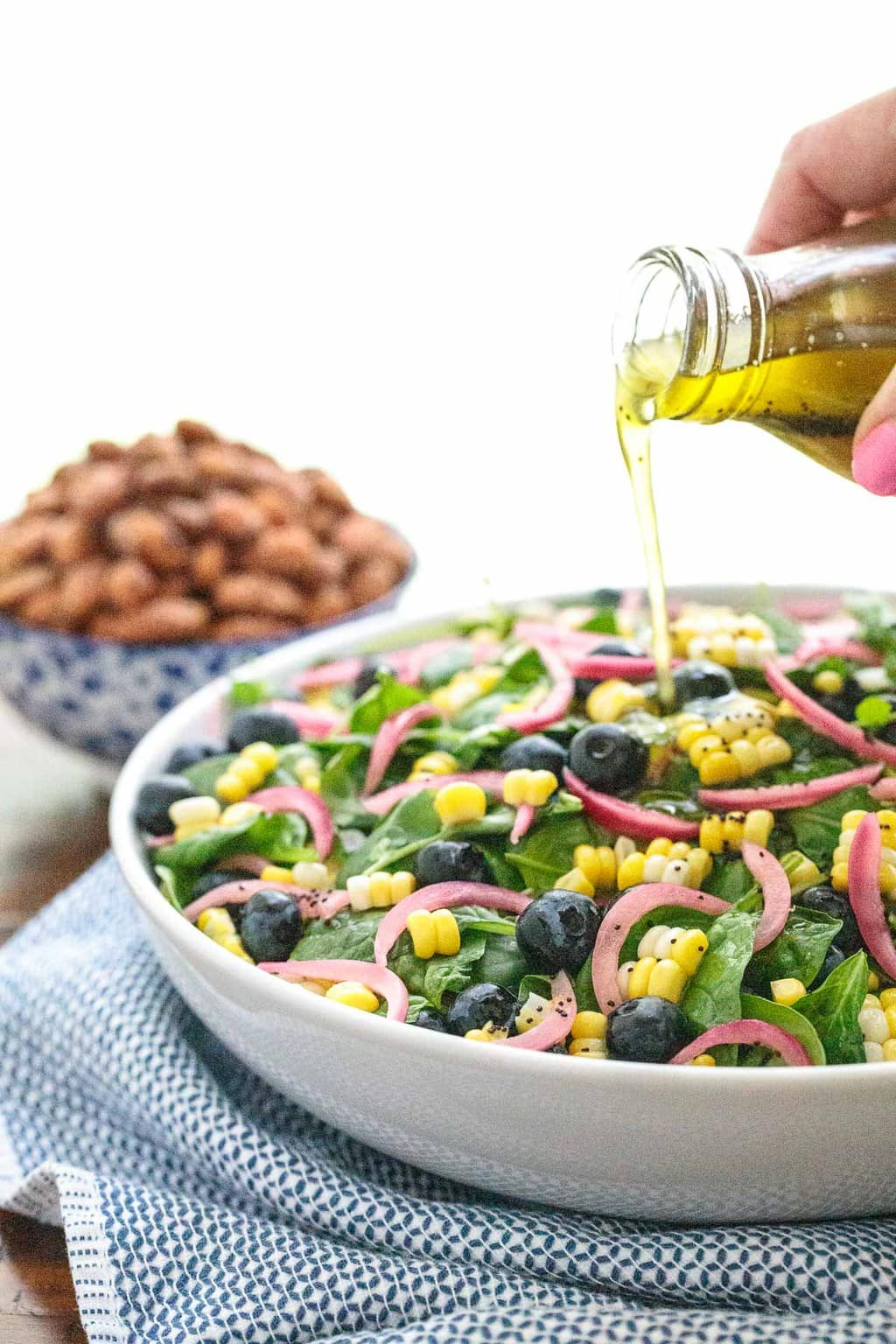 Vertical picture of Blueberry and Fresh Corn Spinach Salad in a white bowl with dressing poured from above