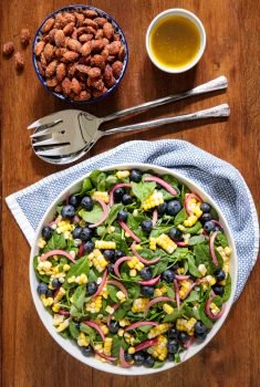 Overhead picture of blueberry and fresh corn salad in a white bowl with tongs and a small bowl of almonds