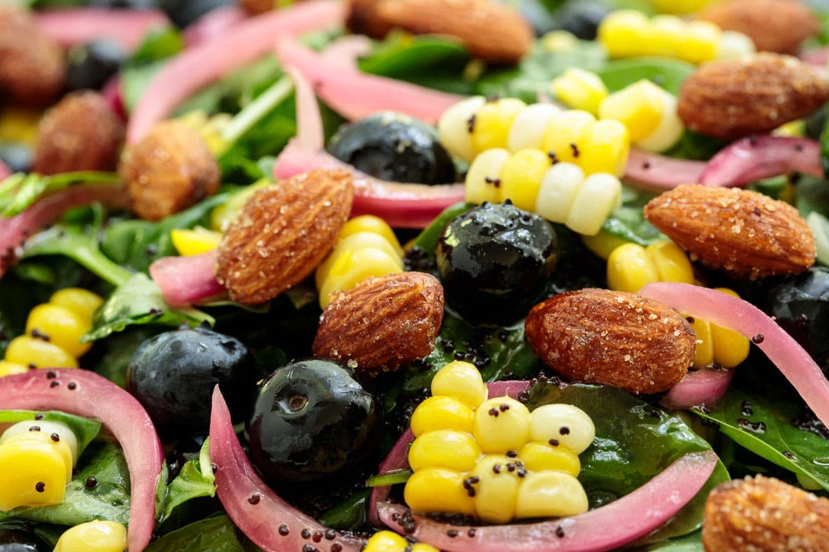 Ultra closeup photo of a Fresh Corn Blueberry Spinach Salad.