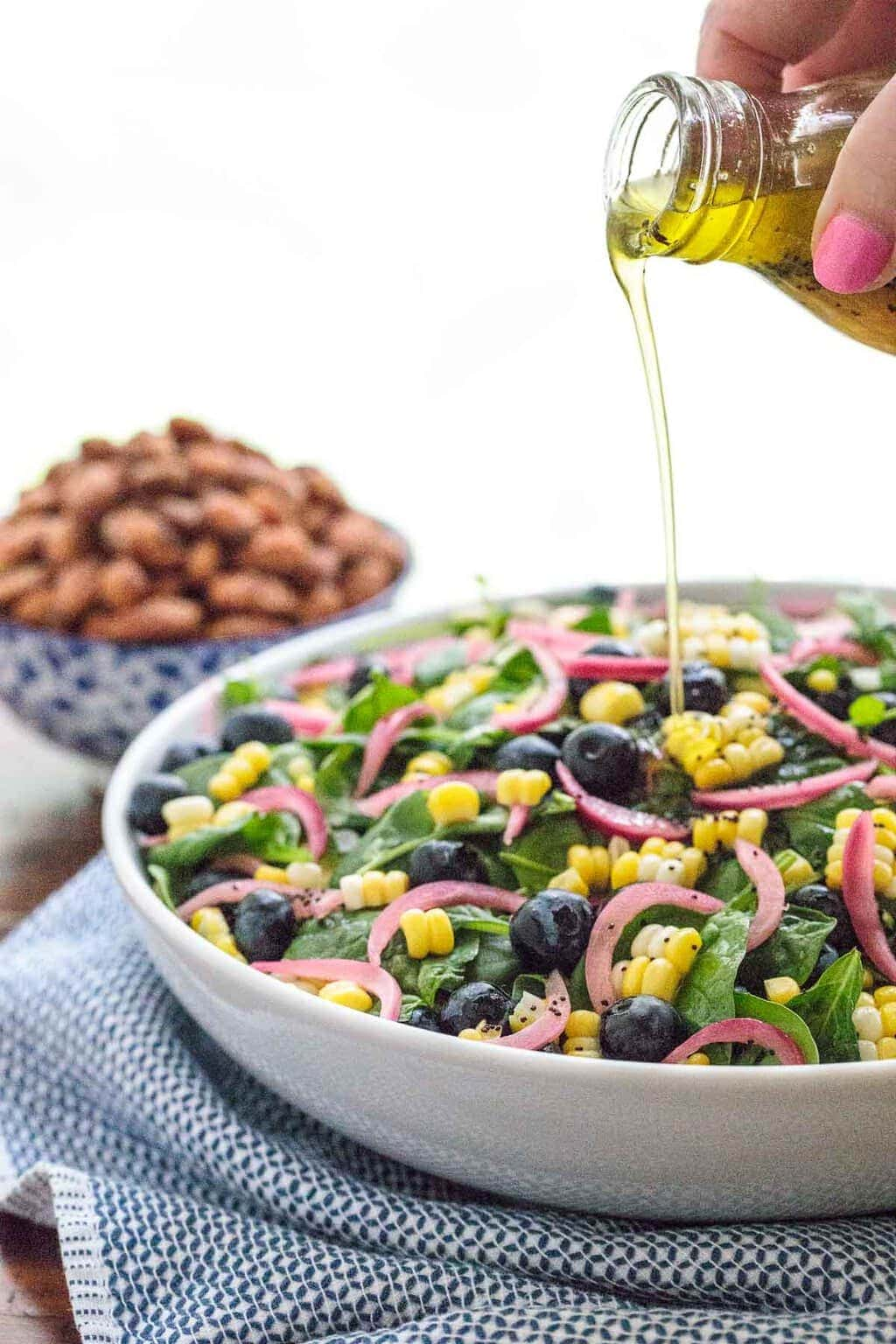 Vertical photo of a Blueberry Spinach Salad in a white serving bowl.