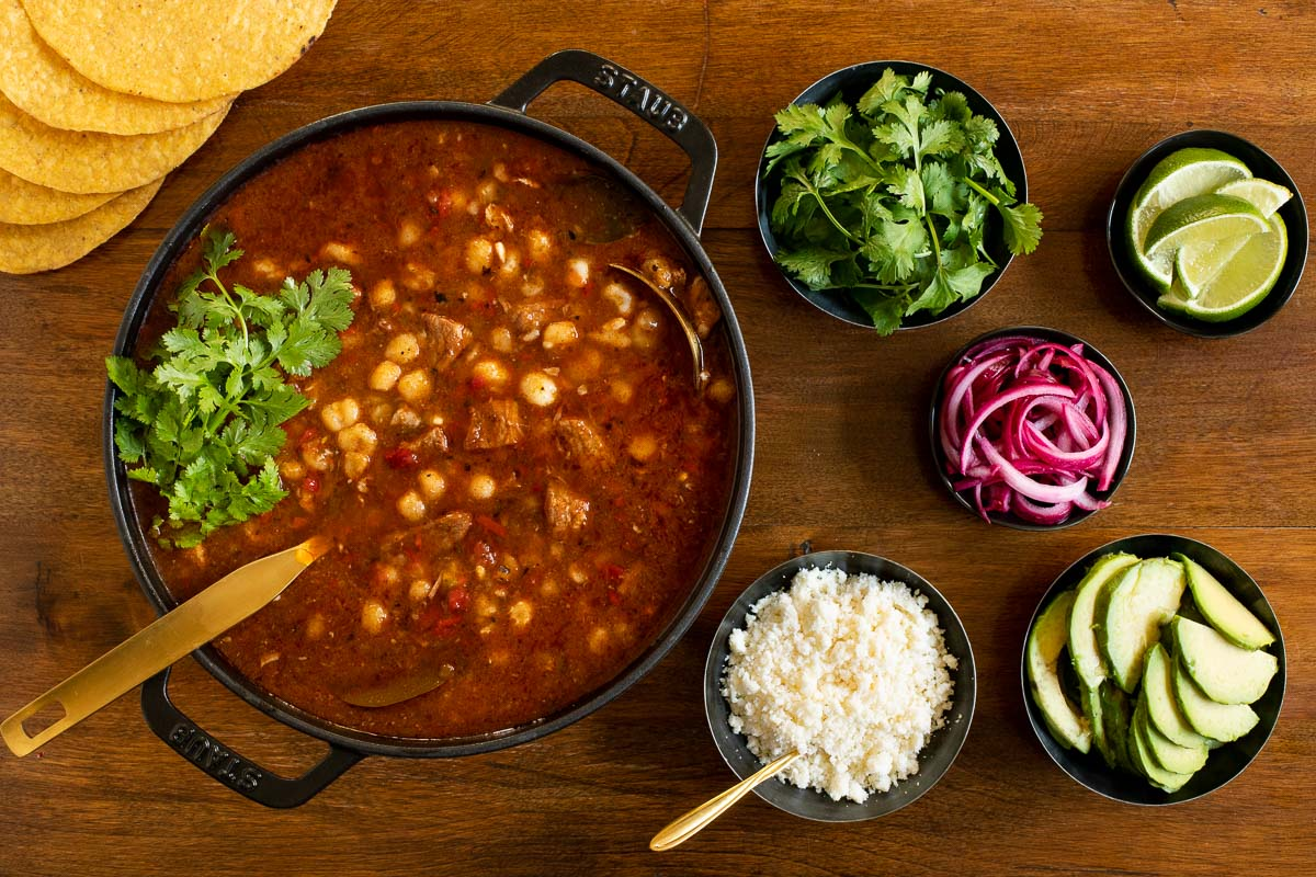 Overhead horizontal photo of a Staub cast iron cooker filled with Braised Pork Shoulder Pozole surrounded by small dishes of garnishes on a wood table.