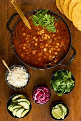 Vertical overhead photo of a pot of Braised Pork Shoulder Pozole on a wood table.