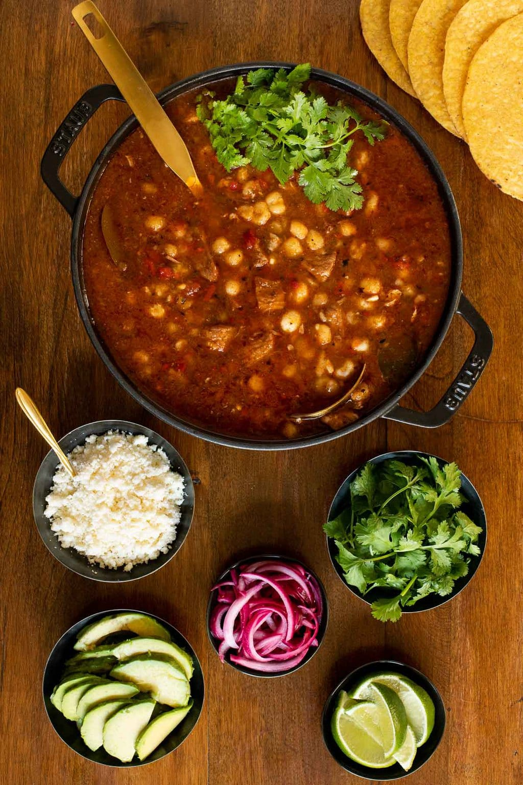 Overhead vertical photo of a Staub cast iron cooker filled with Braised Pork Shoulder Pozole and surrounded by small dishes of garnishes nearby.