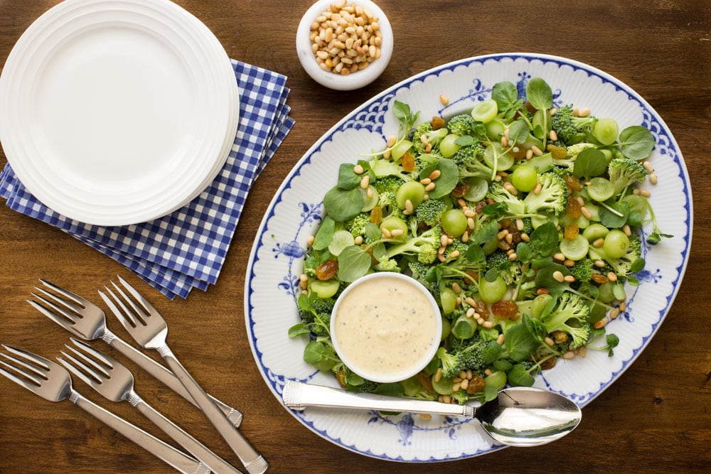 Horizontal overhead view of Broccoli Salad with Grapes and Watercress on a blue and white platter. thecafesucrefarine,com