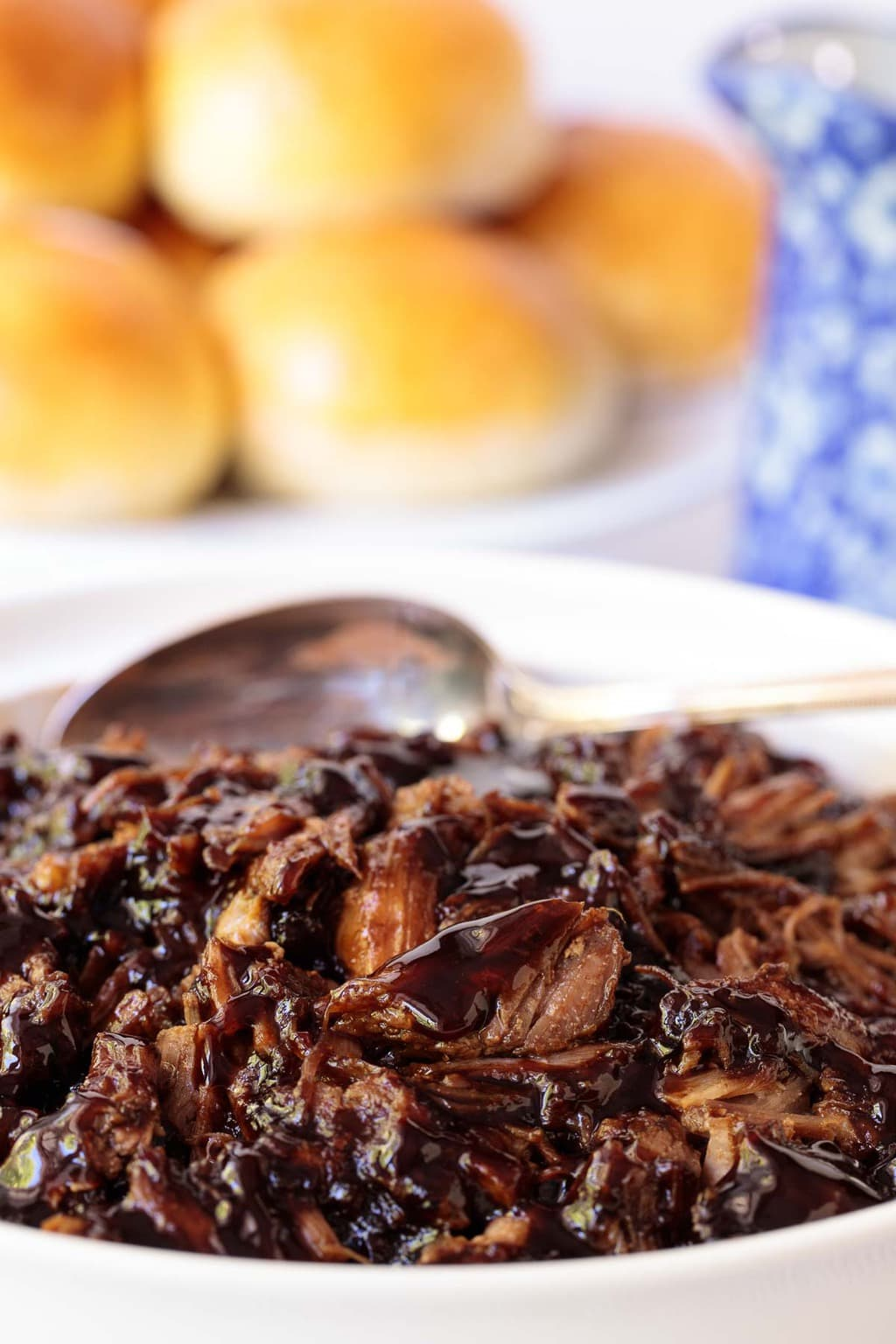 Closeup of a white serving dish filled with Brown Sugar Balsamic Pulled Pork. A plate of homemade brioche buns are in the background.