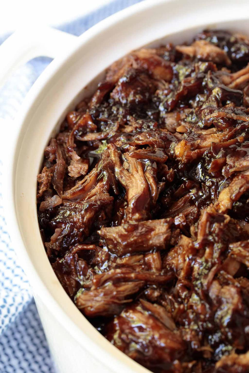 Overhead view of pulled pork with a brown sugar balsamic sauce in a white bowl