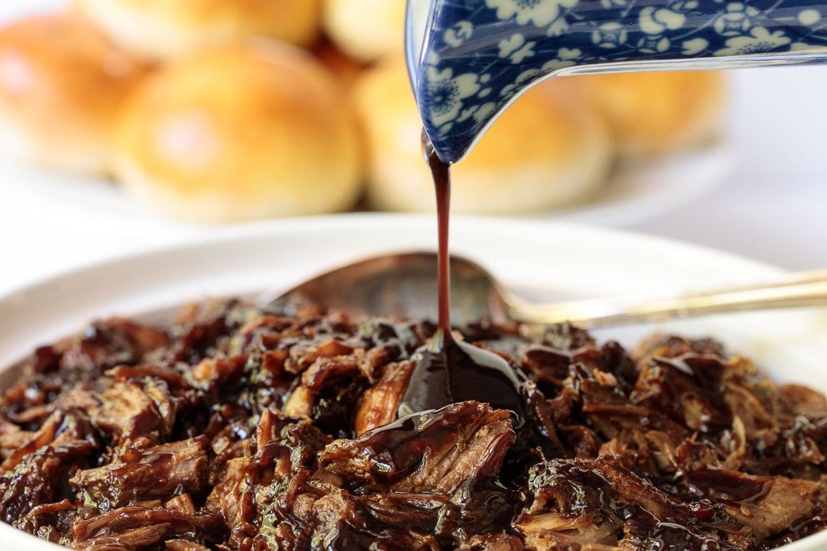Closeup photo of a bowl of Brown Sugar Balsamic Pulled Pork with balsamic sauce being poured over it.