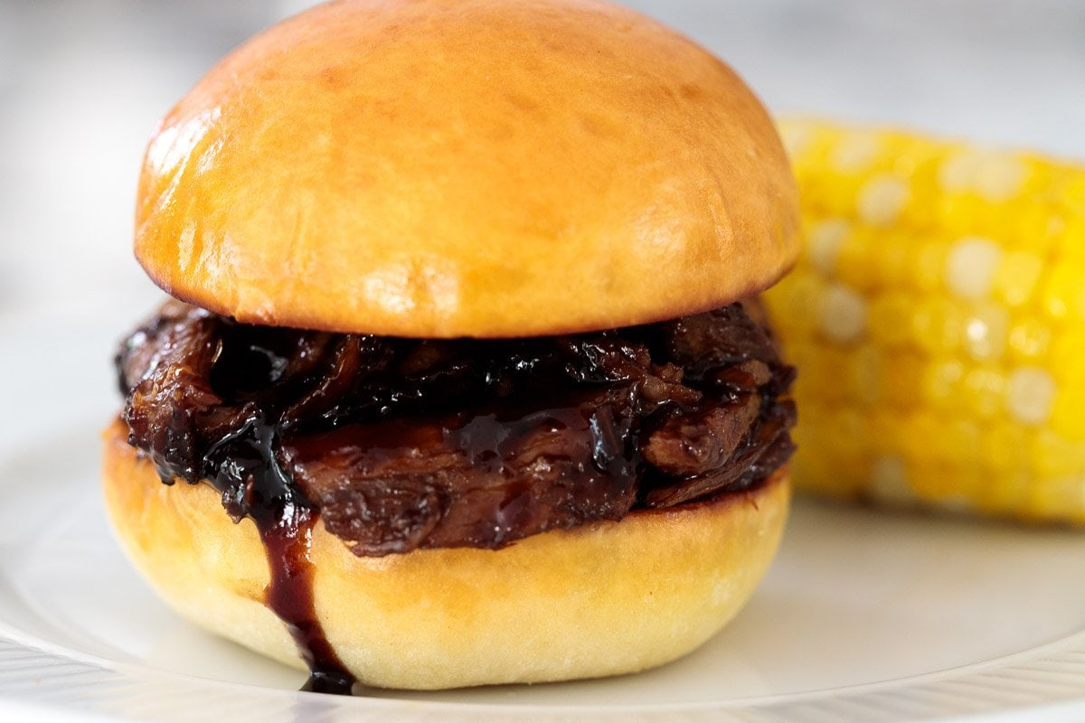Close up of a Buttermilk Brioche Bun with Brown Sugar Balsamic Pulled Pork and an ear of corn in the background.