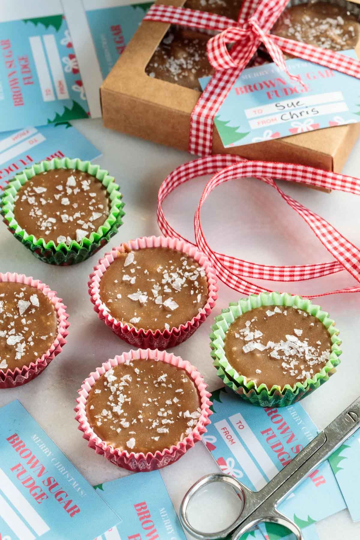 Photo of cups of Sea Salted Brown Sugar Fudge surrounded by gift boxes, labels and ribbon.