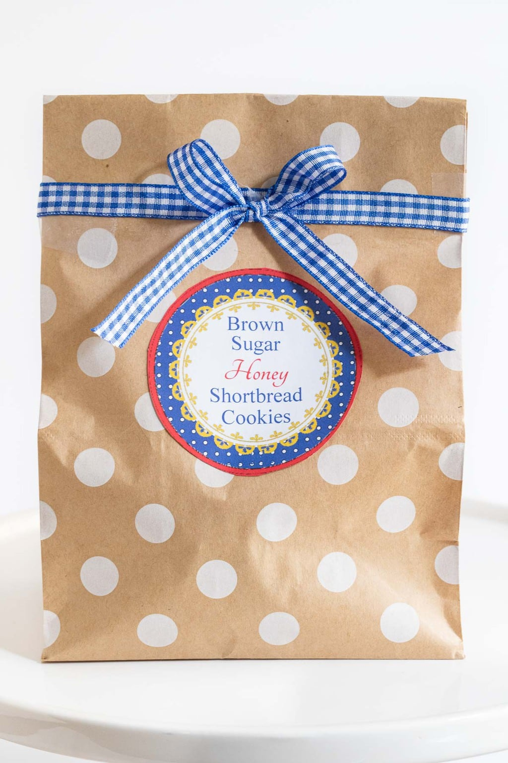 Closeup vertical photo of a polka dot paper gift bag decorated with a Brown Sugar Honey Shortbread Cookies label and blue and white checkered ribbon in a bow.