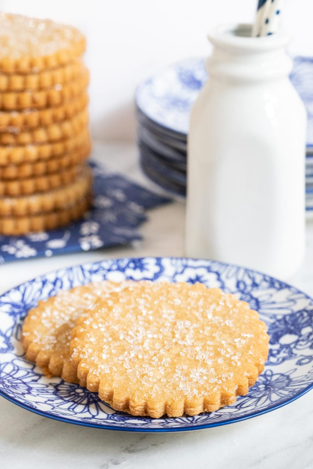 Vertical photo of a plate of Brown Sugar Honey Shortbread Cookies with a stack of the cookies in the background.