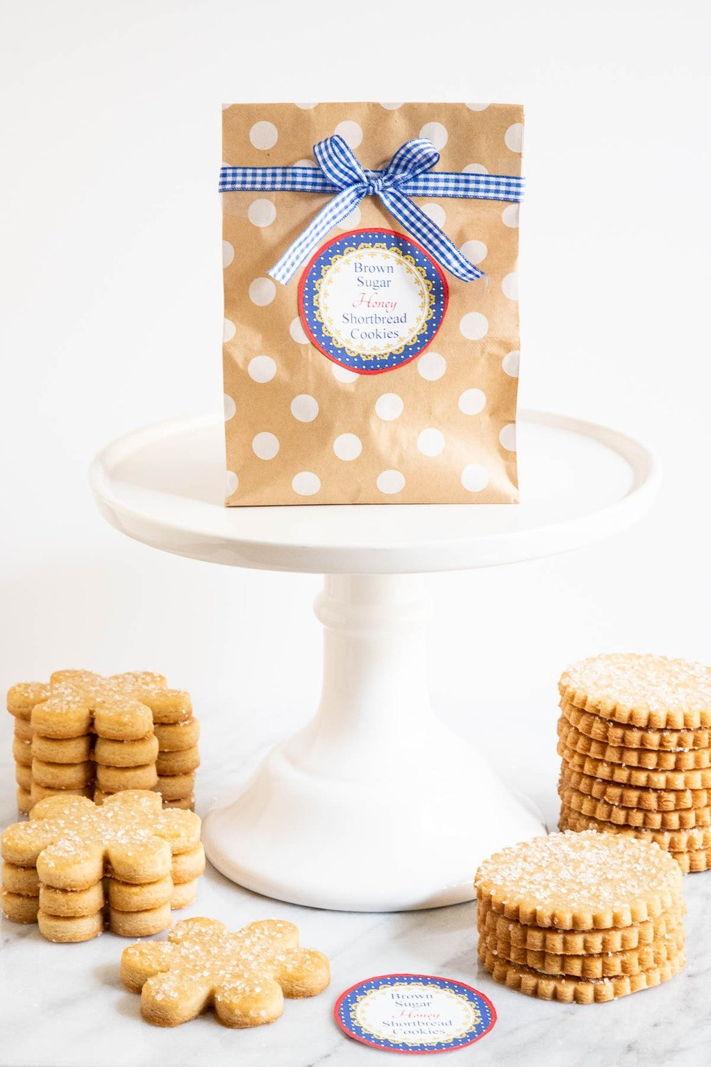 Vertical photo of a gift bag filled with Brown Sugar Honey Shortbread Cookies on a white pedestal cake stand with stacks of the cookies piled in front of the stand and a label for the cookies on the bag.