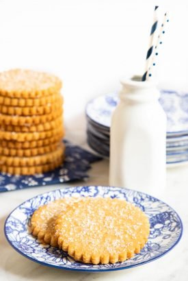Vertical photo of two Brown Sugar Honey Shortbread Cookies on a plate with a stack of the cookies and a pint of milk in the background.