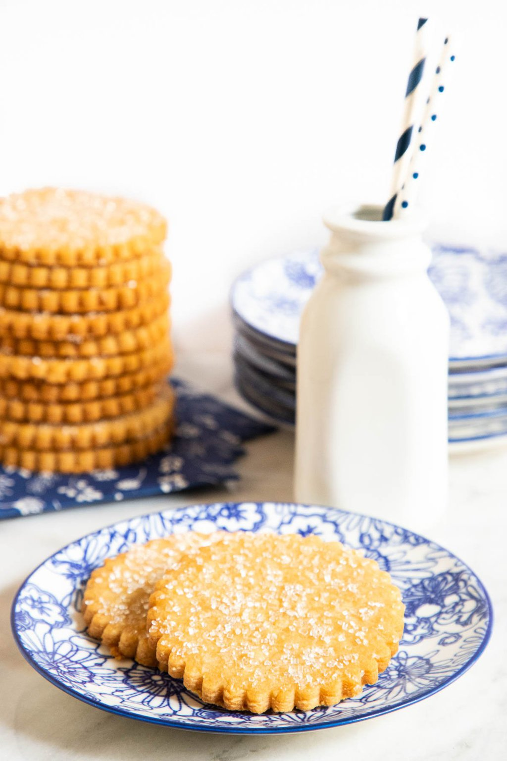 Vertical photo of a plate with two Brown Sugar Honey Shortbread Cookies and a stack of the cookies with milk in the background.