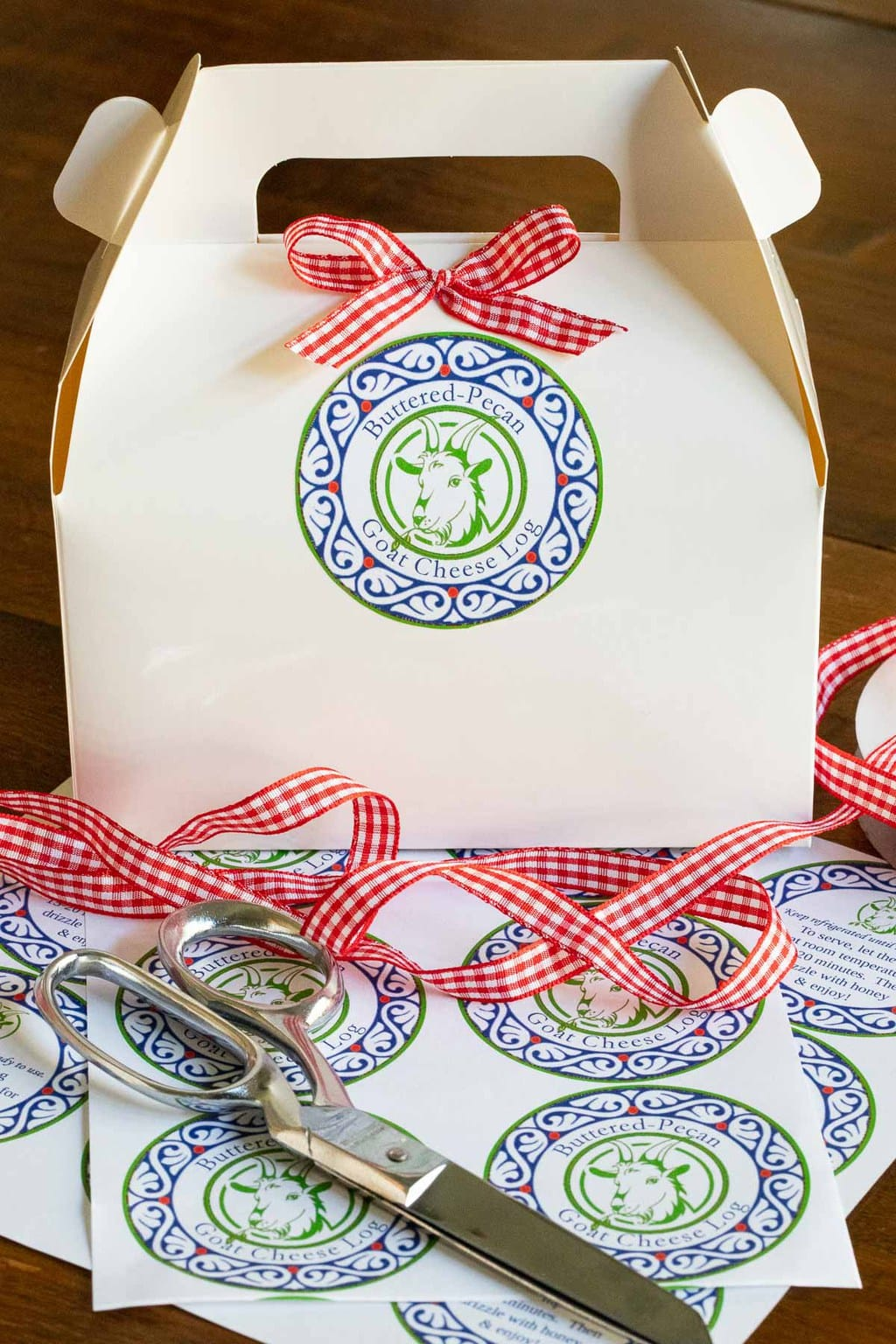 A vertical photo of custom Buttered Pecan Goat Cheese Log labels and instructions for gift giving. In the background is a white gift box.