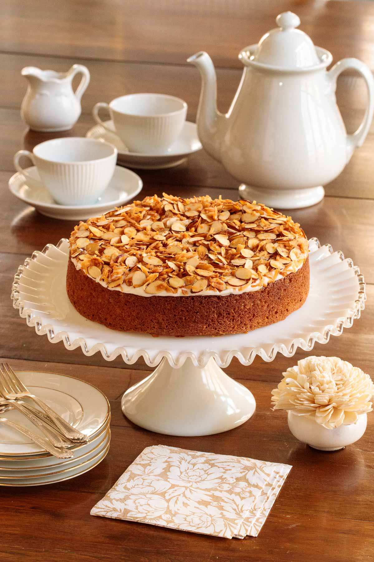 Photo of an Easy Buttermilk Butter Crunch Cake on a white glass pedestal stand surrounded by a tea set and serving items.