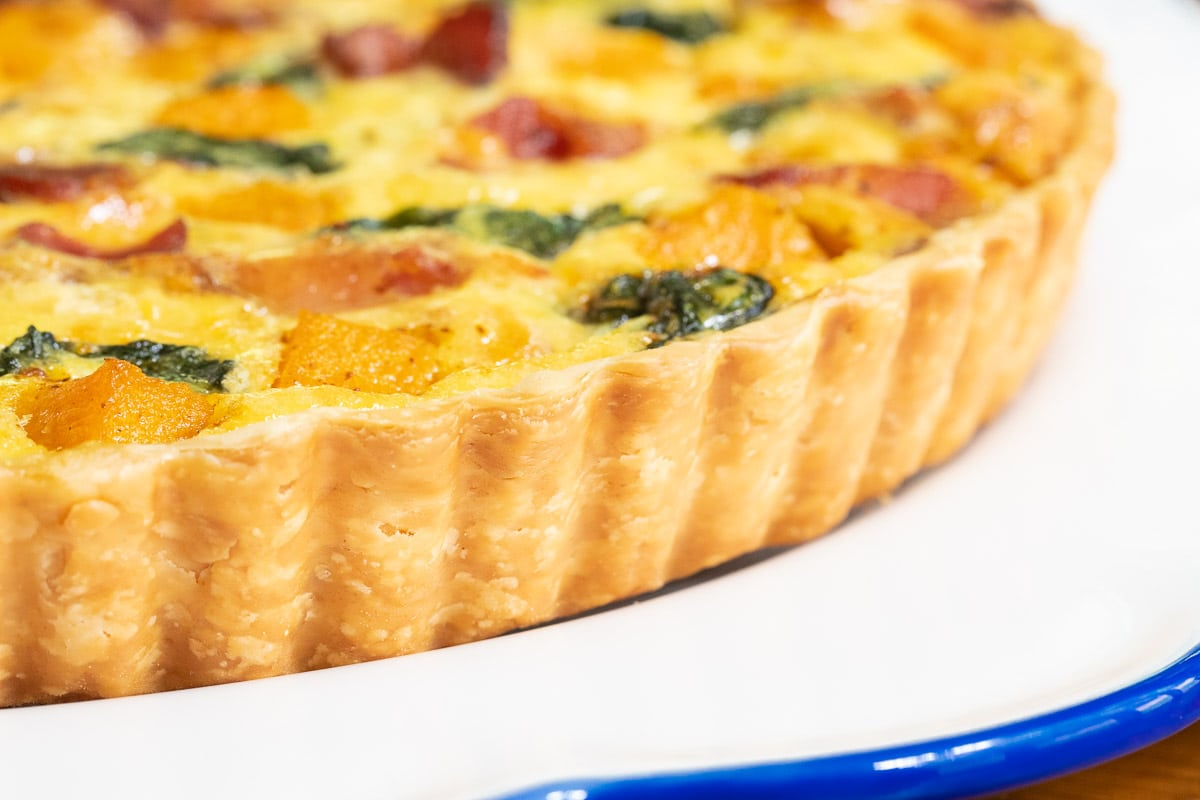 Extreme horizontal closeup photo of the crust and side of an Butternut Bacon Spinach Quiche.