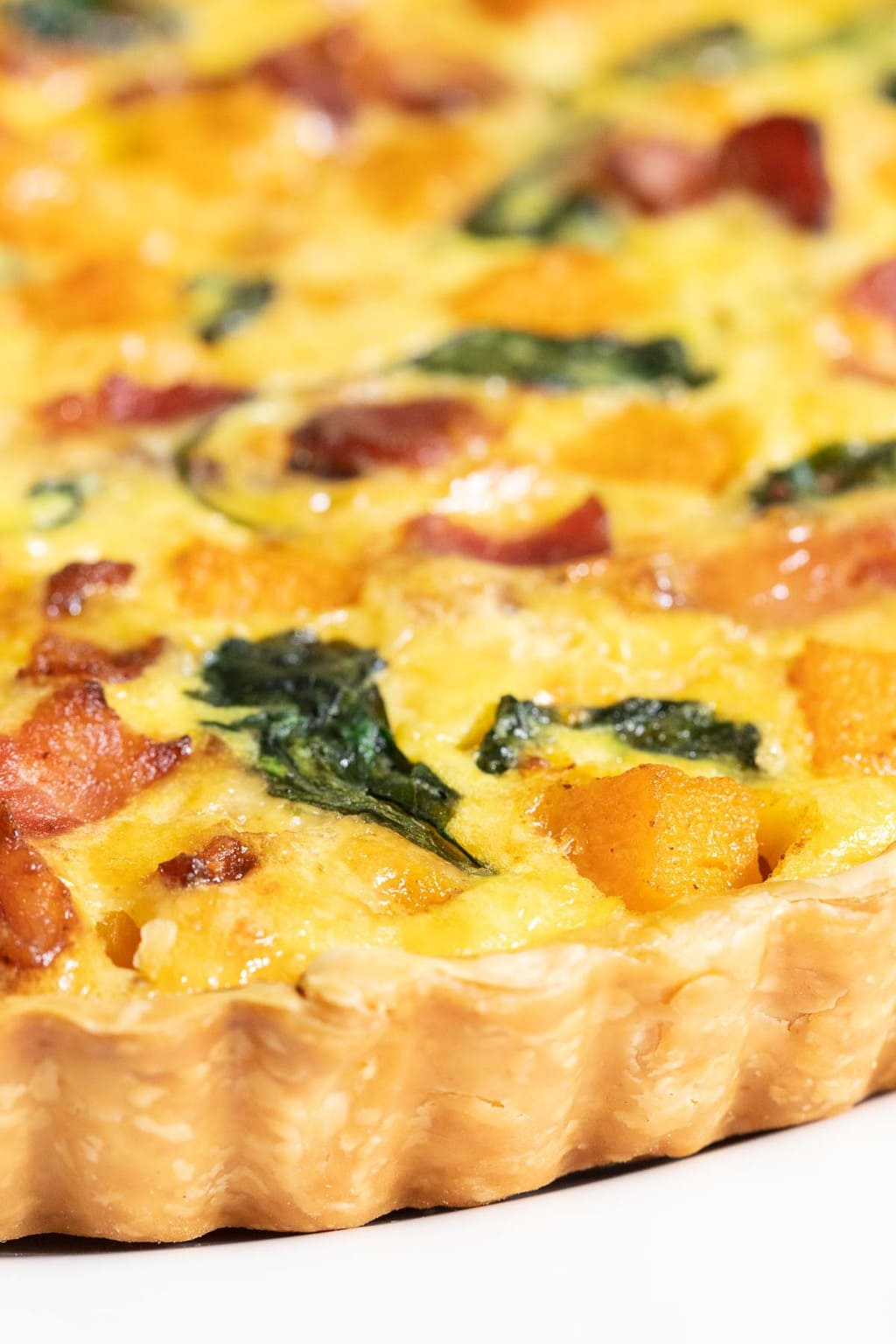 Extreme vertical closeup photo of an Butternut Bacon Spinach Quiche.