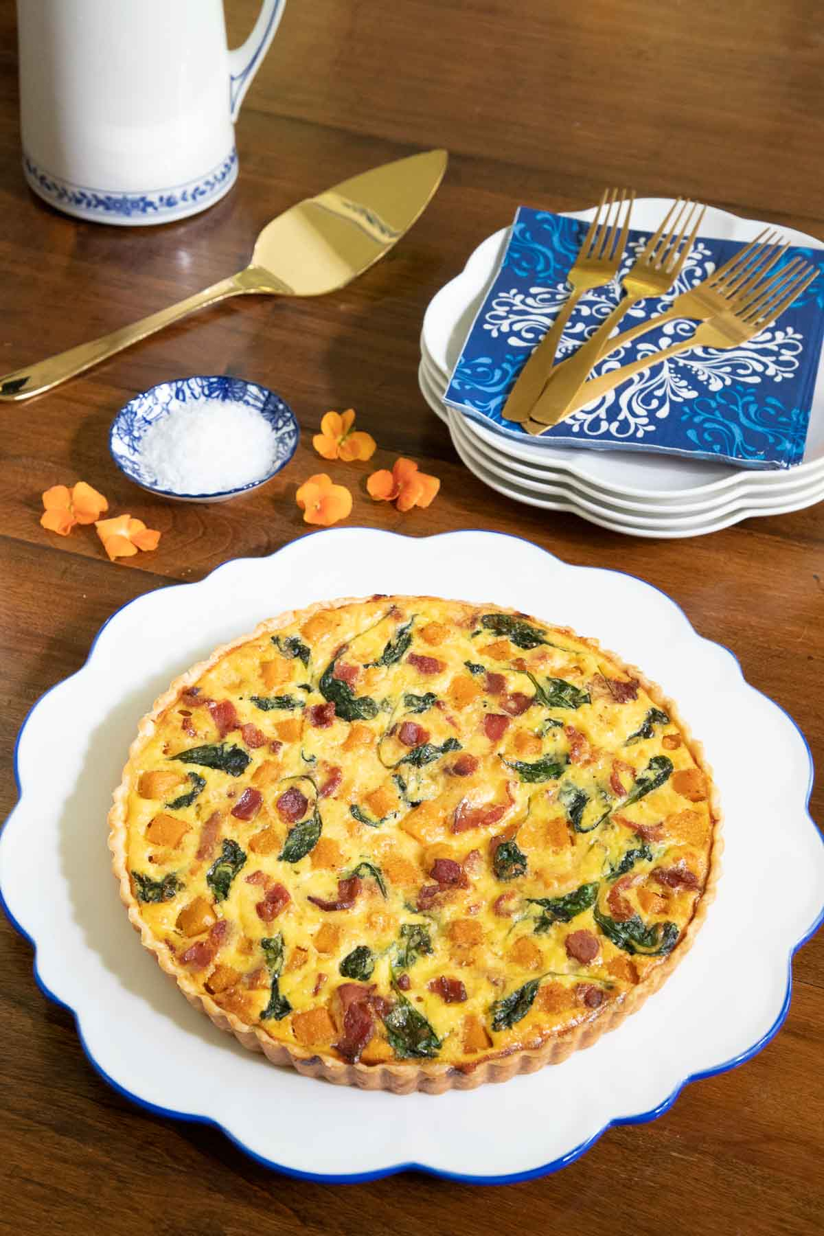 Vertical photo of an Butternut Bacon Spinach Quiche on a scalloped presentation plate on a wood dining table.
