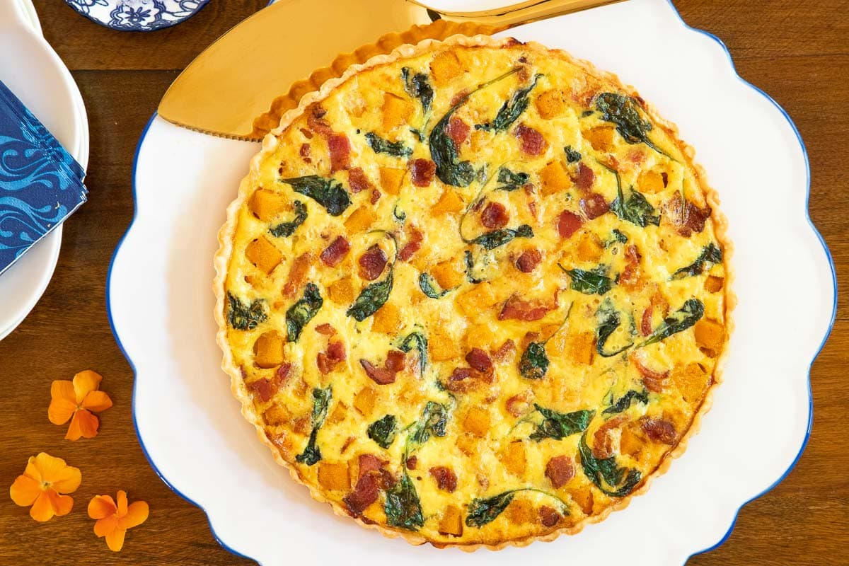 Closeup overhead horizontal photo of a Butternut Bacon Spinach Quiche.