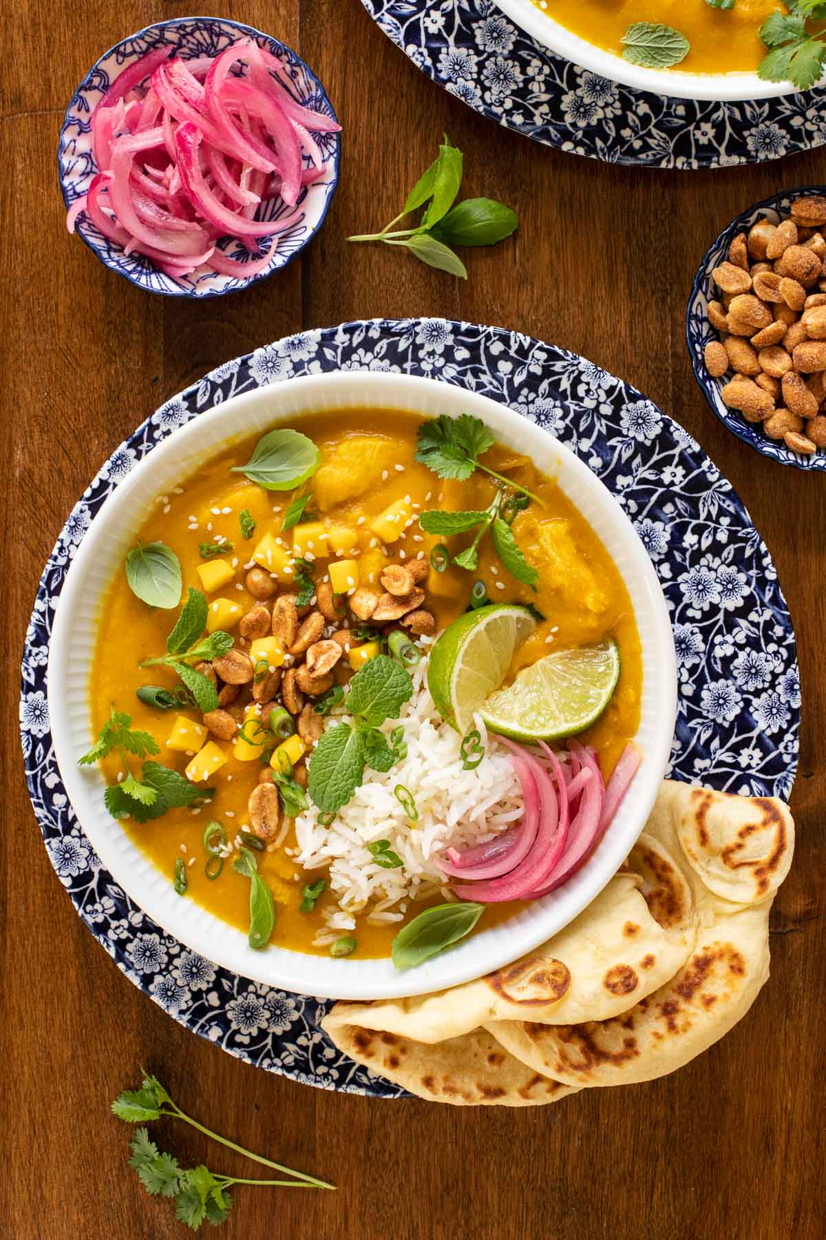 Overhead vertical photo of Butternut Chicken Coconut Curry in a blue and white patterned serving bowl garnished with toppings and naan bread on the side.