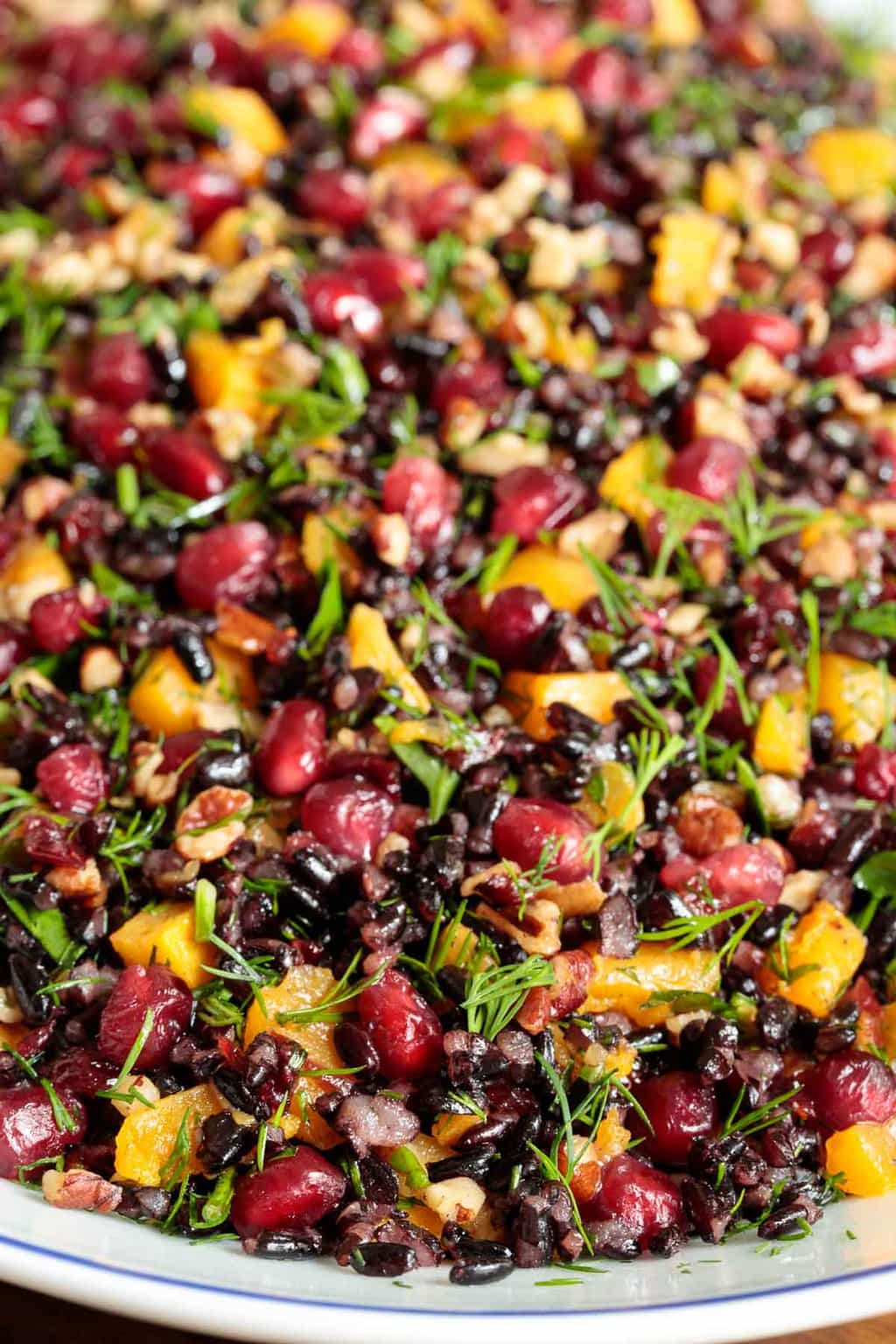Extreme closeup photo of a platter of Butternut Squash Black Rice Salad.