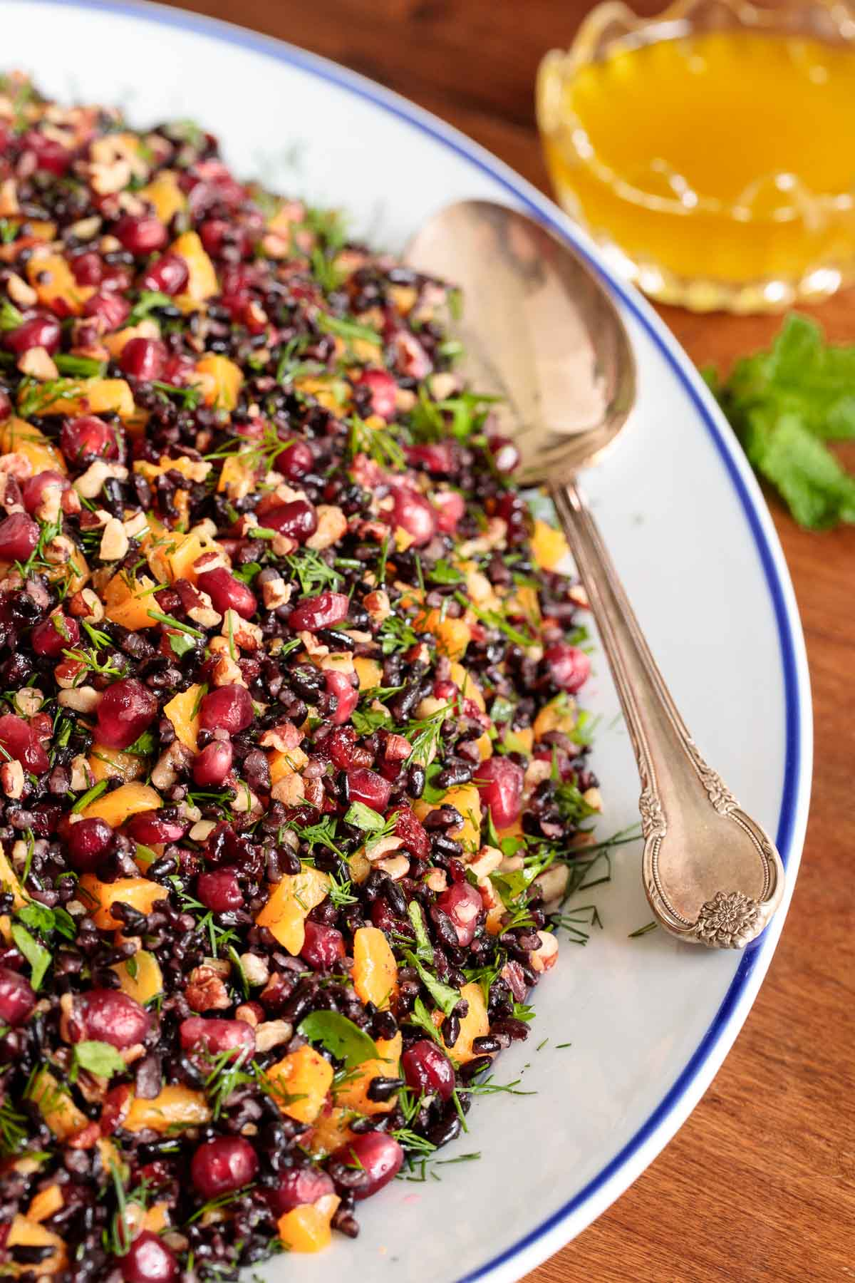 Vertical closeup photo of a Butternut Squash Black Rice Salad on a white serving platter.