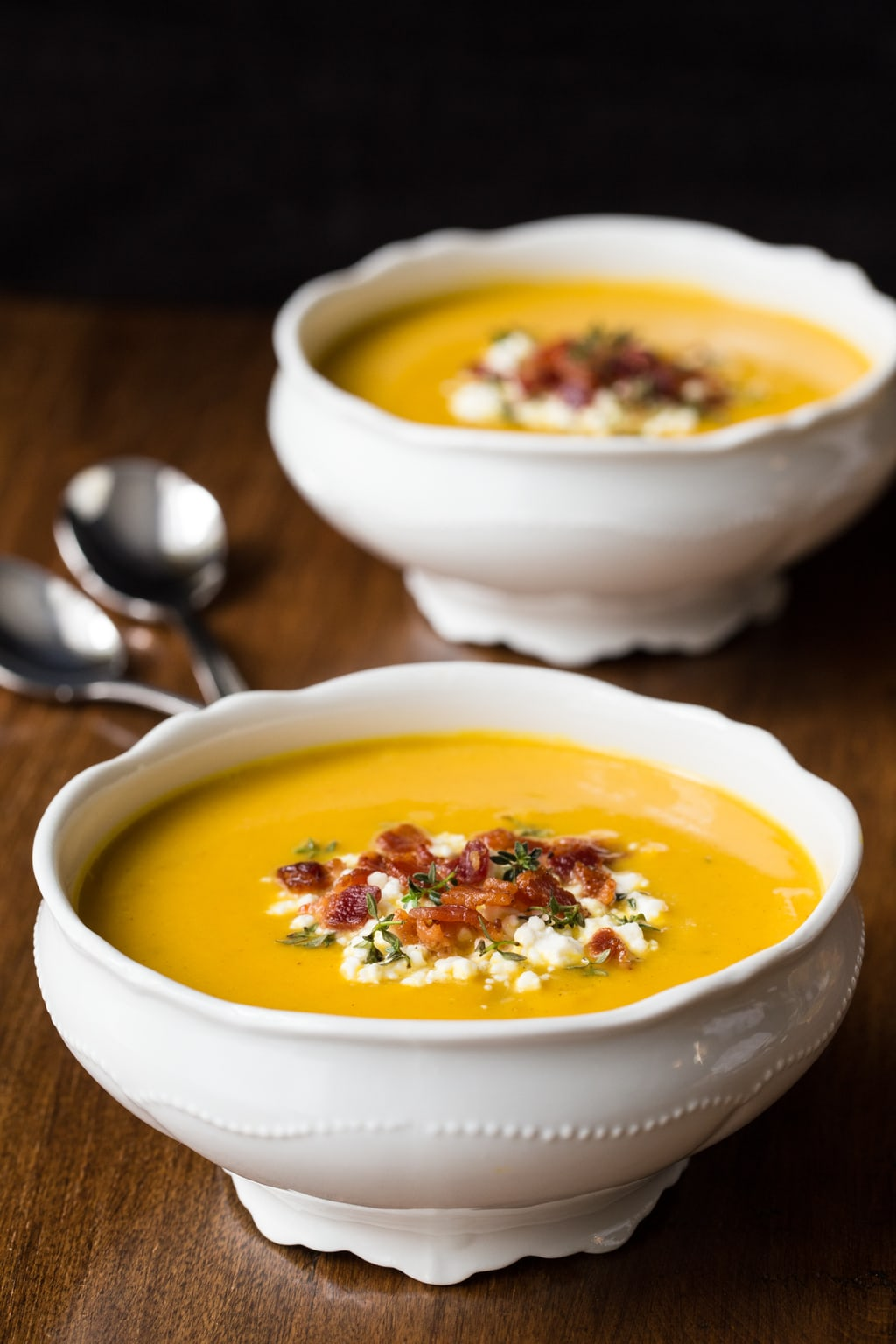 A photo of two white bowls of Butternut Squash and Bacon Soup, one of The Cafe Sucre Farine's Soup Recipes, on a wood table.