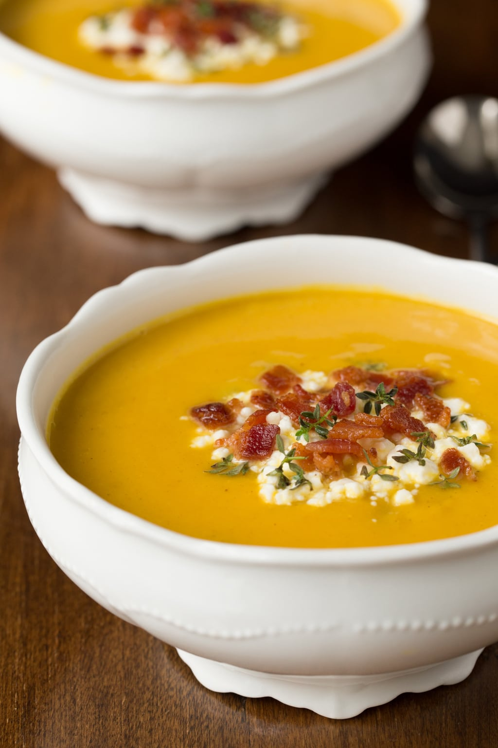 Photo of two white bowls of Butternut Squash and Bacon Soup on a wood table.