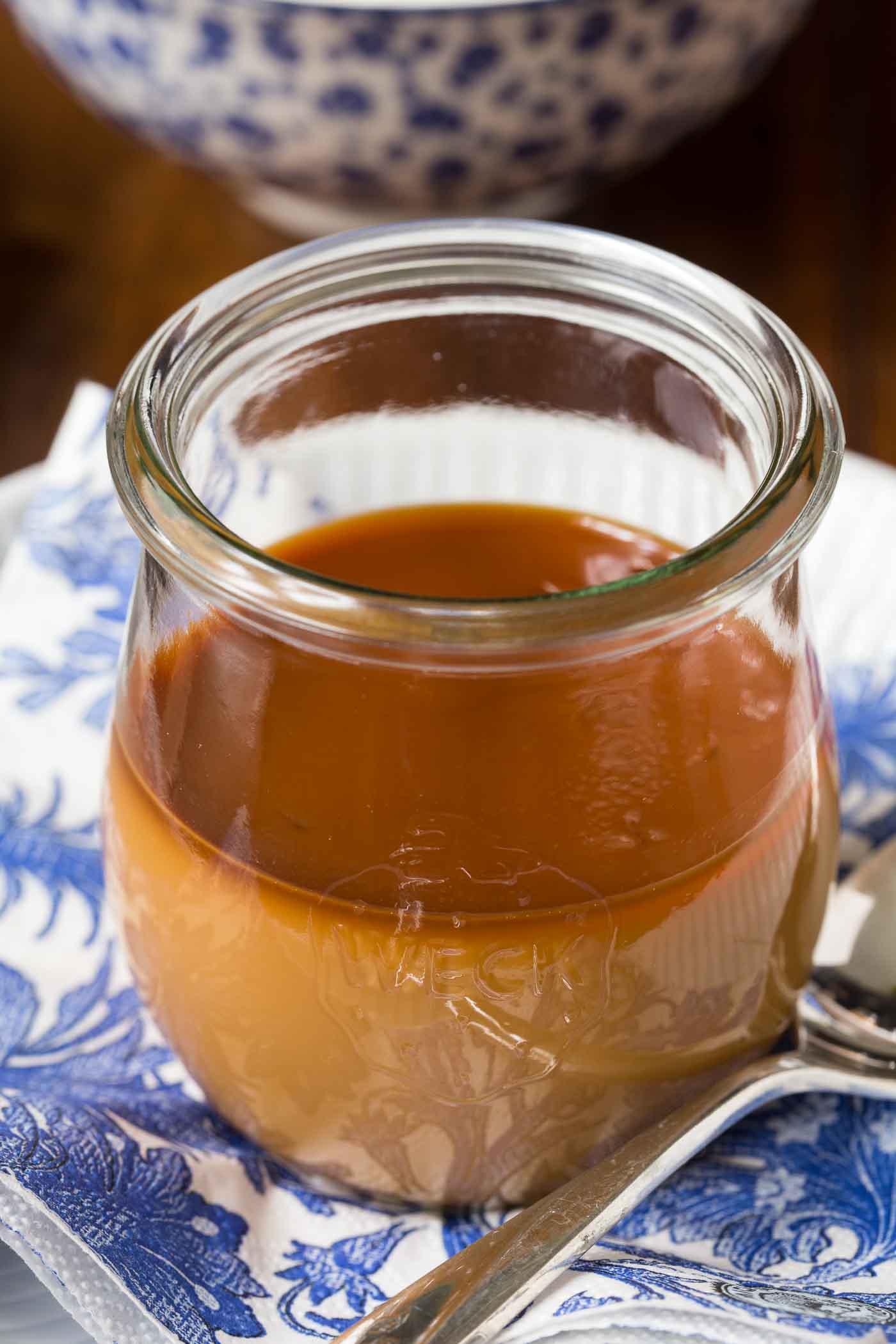Photo of a jar of Butterscotch Pots de Créme on a delft blue and white napkin.