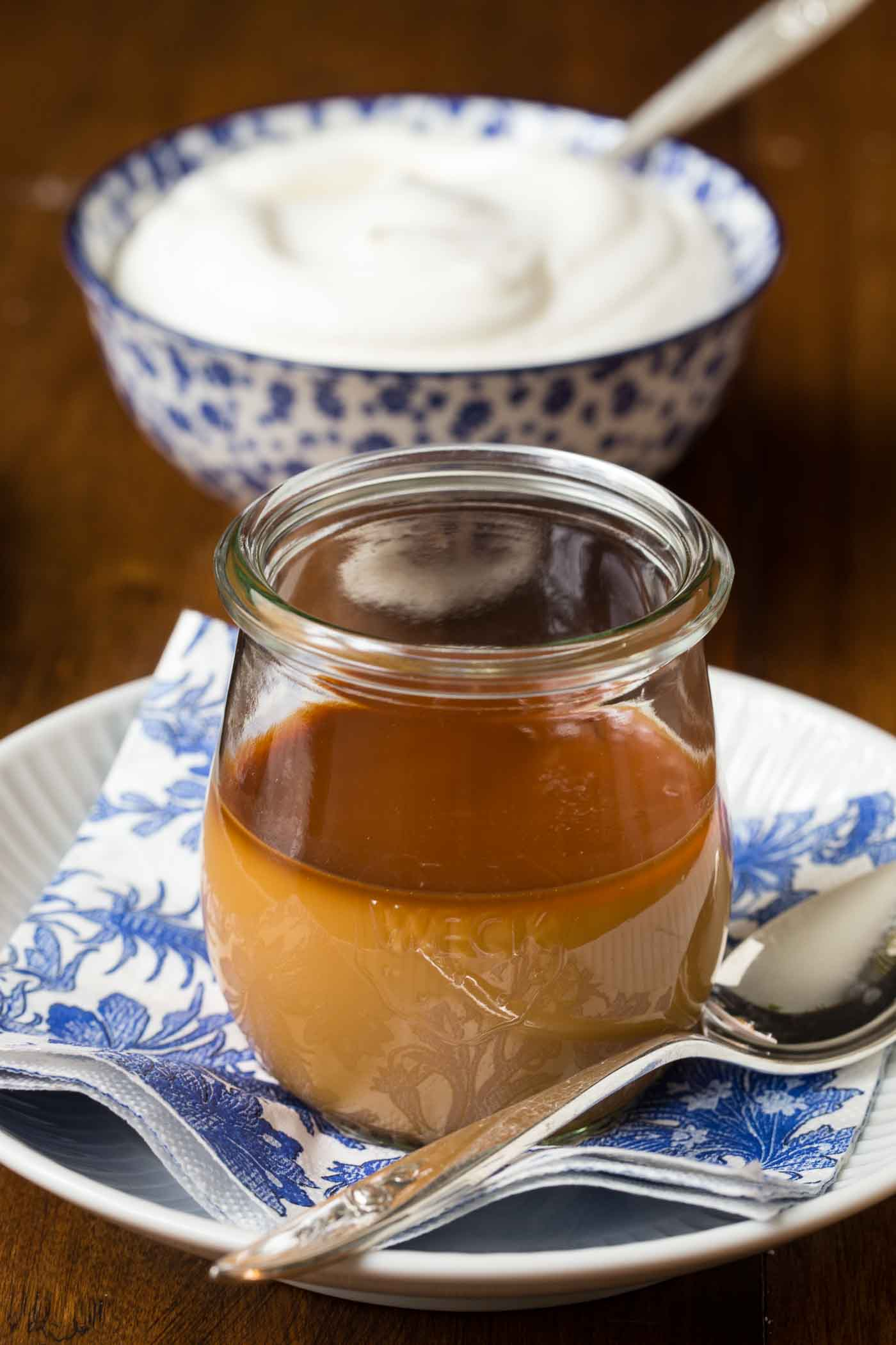 Vertical picture of Butterscotch Pots de Créme in a small glass jar on a blue and white plate with whipped cream in the background