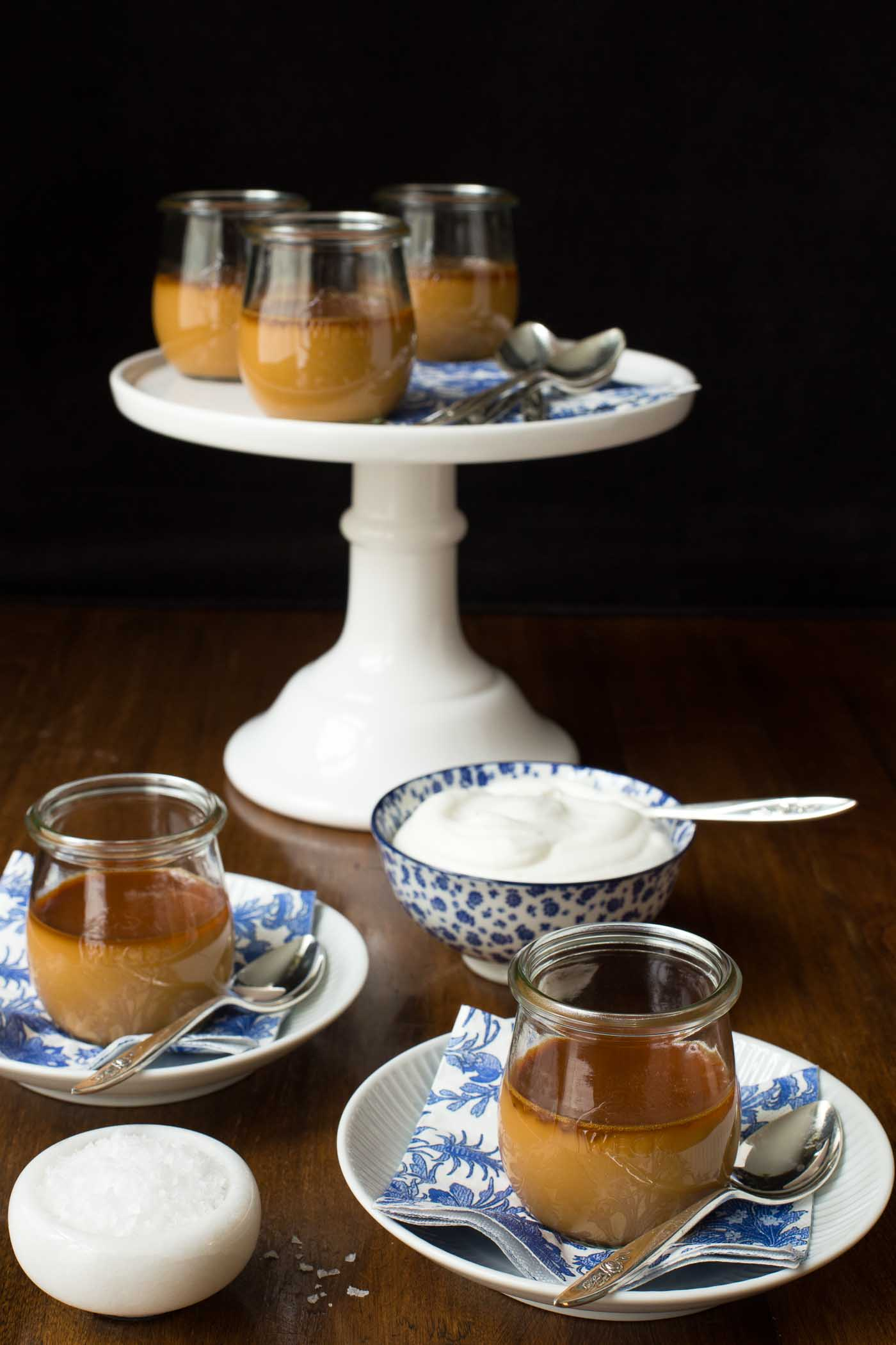 Photo of a set of jars of Butterscotch Pots de Créme on a white pedestal with two jars on serving dishes and napkins in the foreground and two bowls, one of whipped cream and one of sea salt.