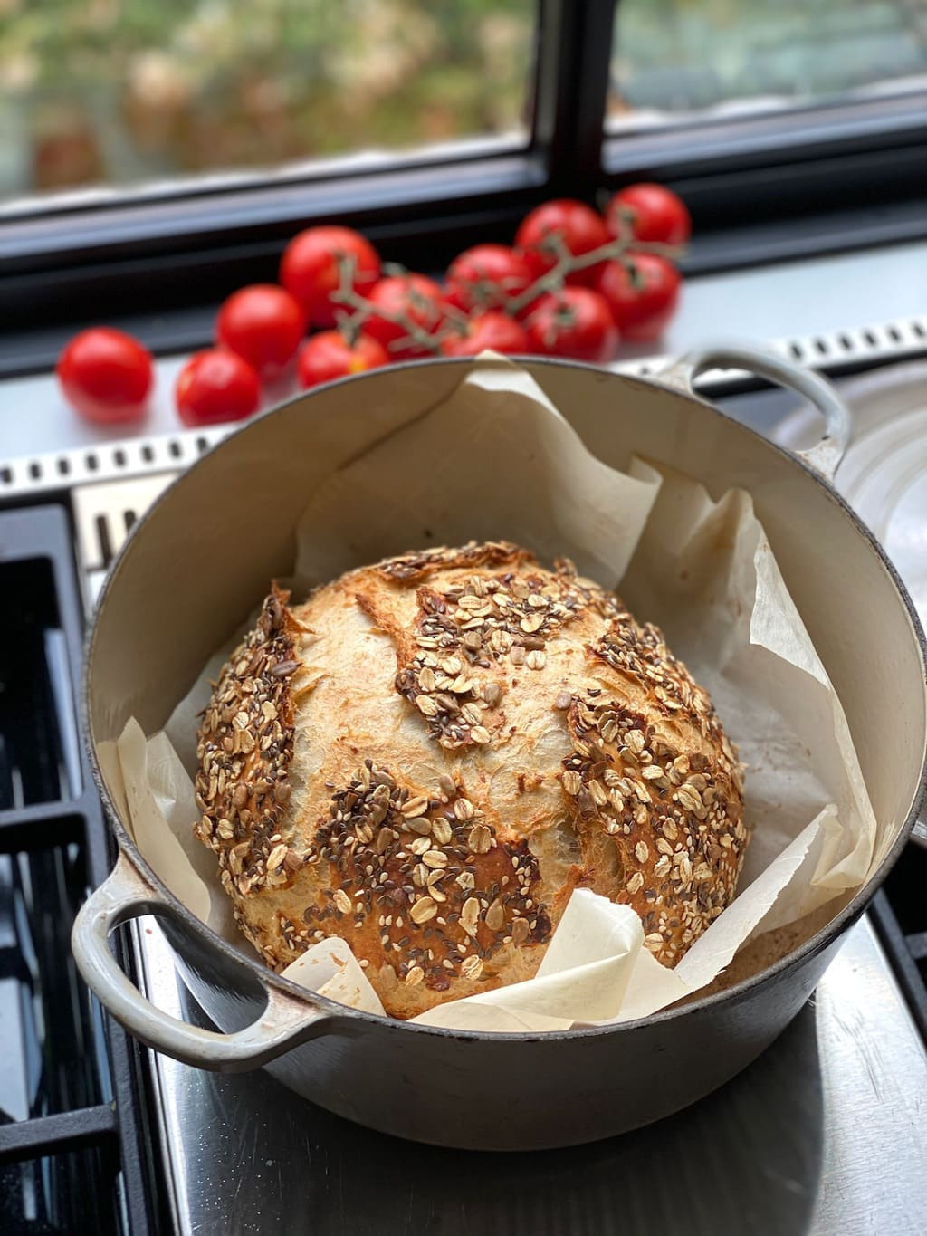 Vertical photo of a loaf of No-Knead Seeded Oatmeal Bread in a baking pot on a stove.