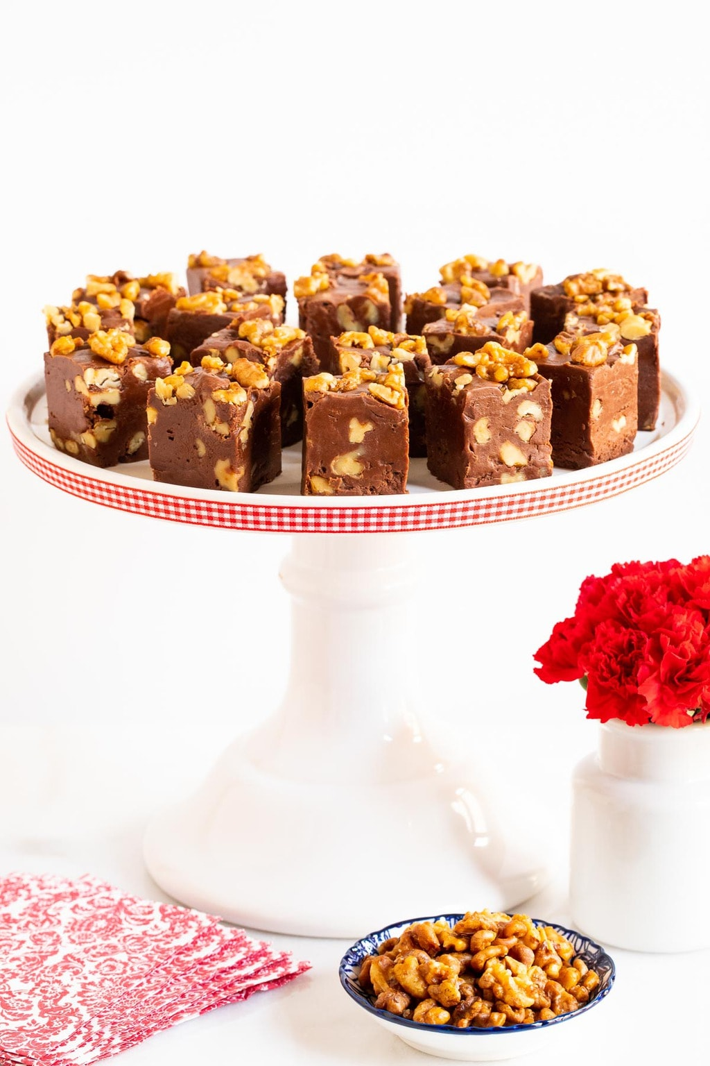 Vertical photo of a white presentation platter of Candied Walnut Chocolate Fantasy Fudge.