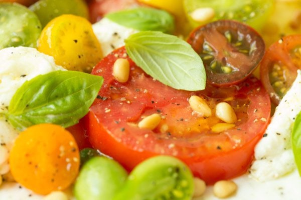 Closeup of a Summer Caprese Salad with tomatoes, basil, feta cheese and pine nuts.