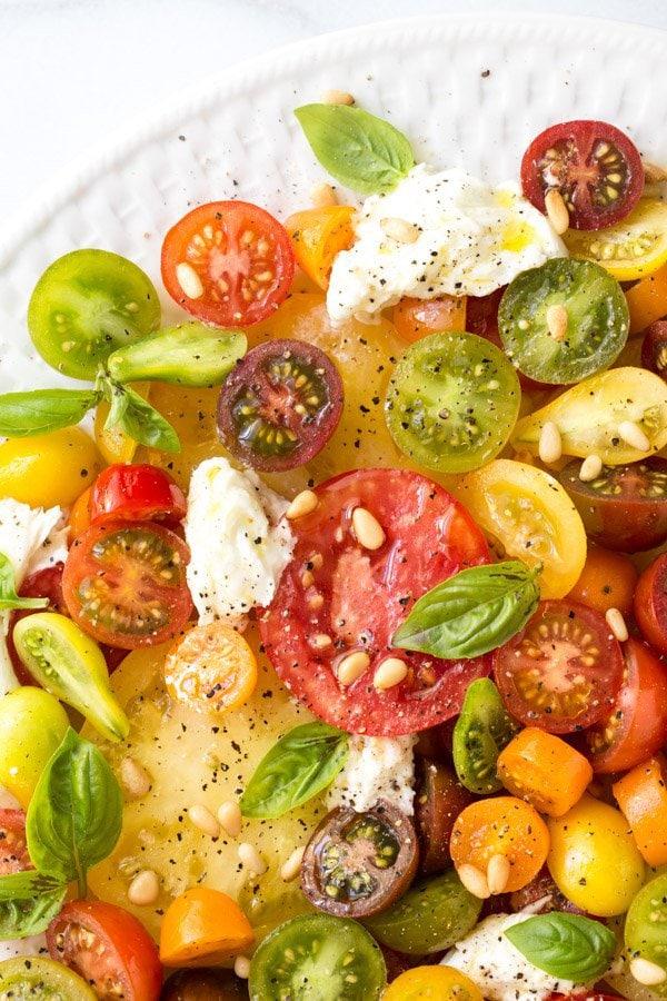 Overhead closeup photo of a Summer Caprese Salad on a white basketweave plate.