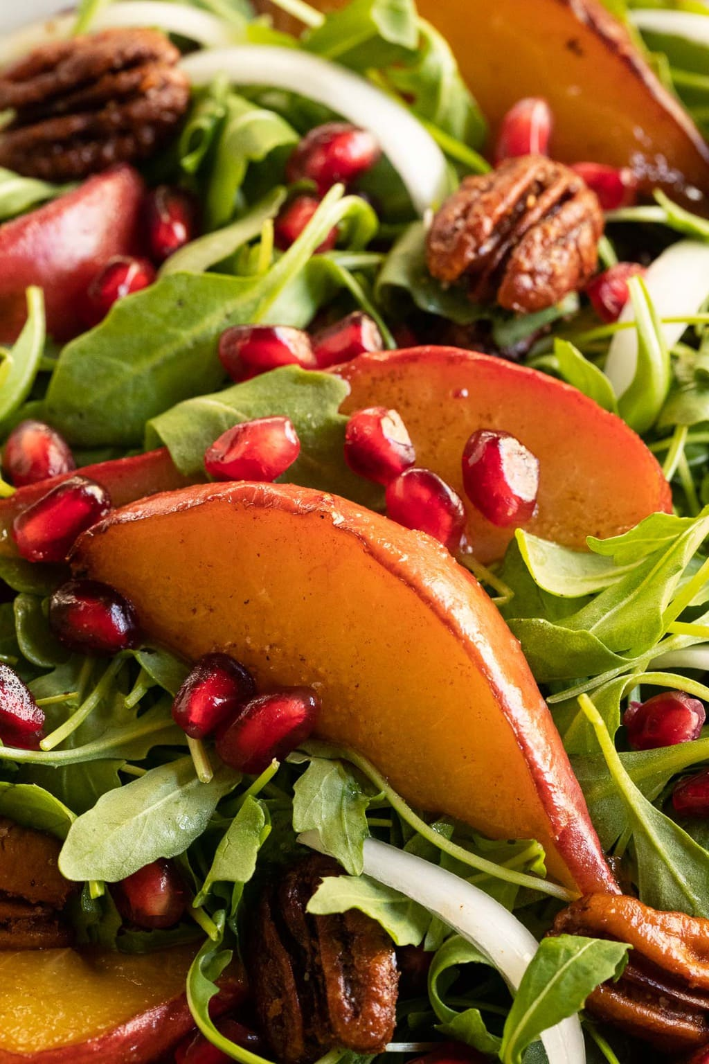 Extreme closeup photo of a Caramelized Pear Arugula Salad featuring pomegranate arils and caramelized pears.