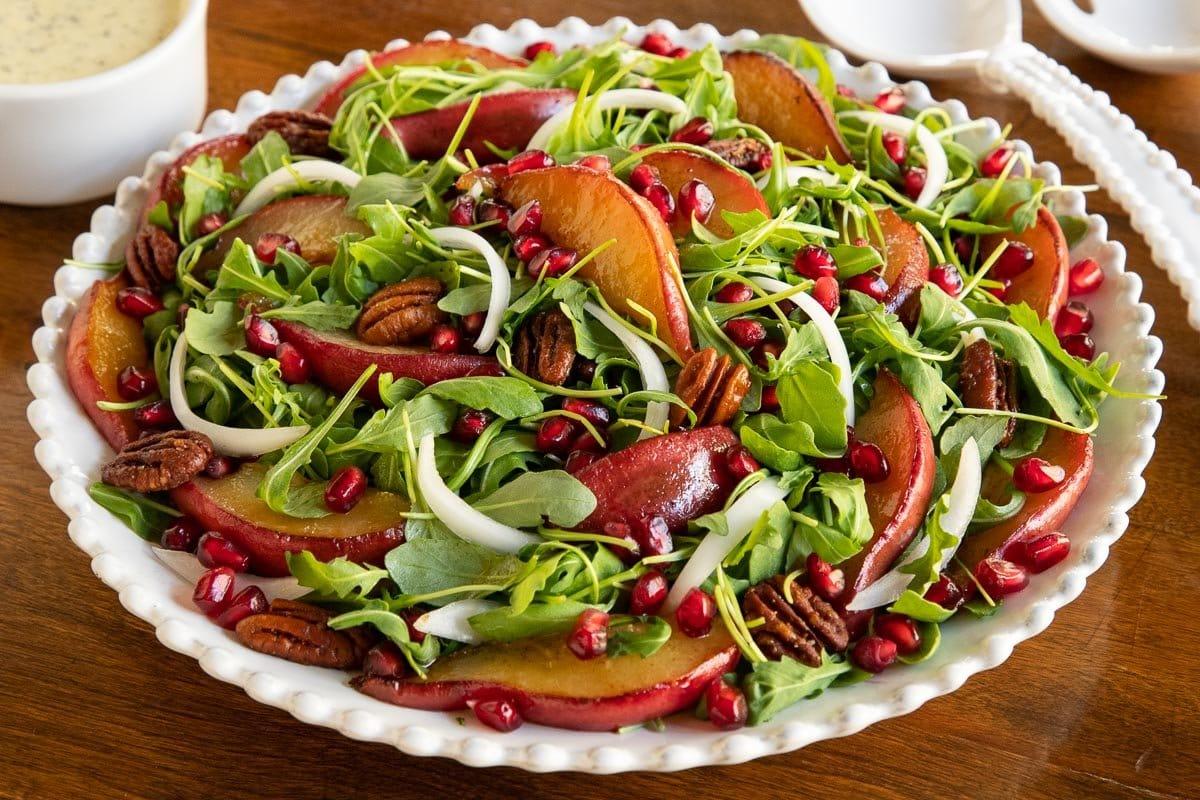 Horizontal closeup photo of a Caramelized Pear Arugula Salad on a wood table.