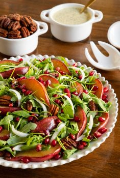 Vertical photo of a Caramelized Pear Arugula Salad on a wood table.