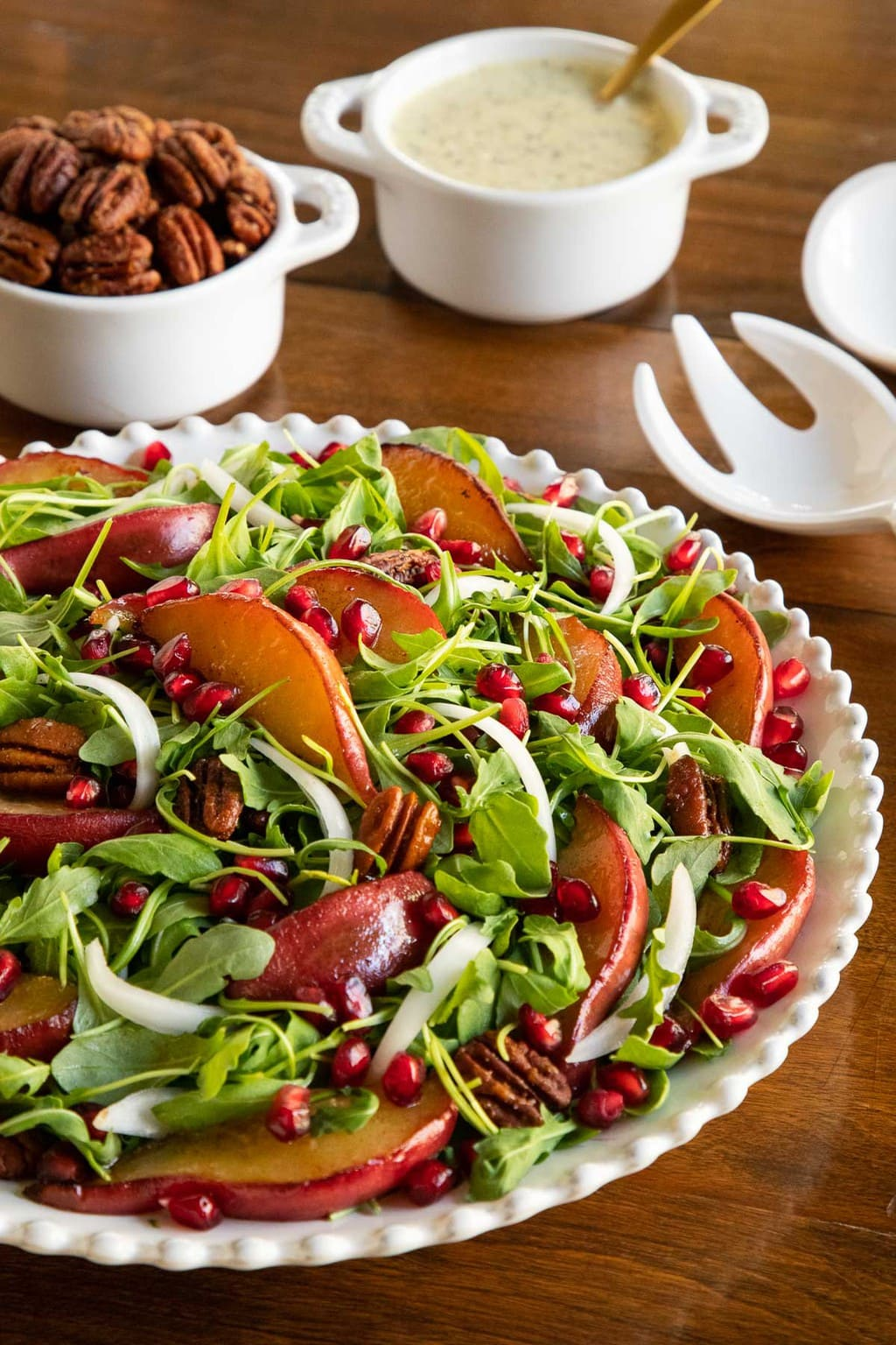 Vertical photo of a Caramelized Pear Arugula Salad on a white scalloped serving plate on a wood table.