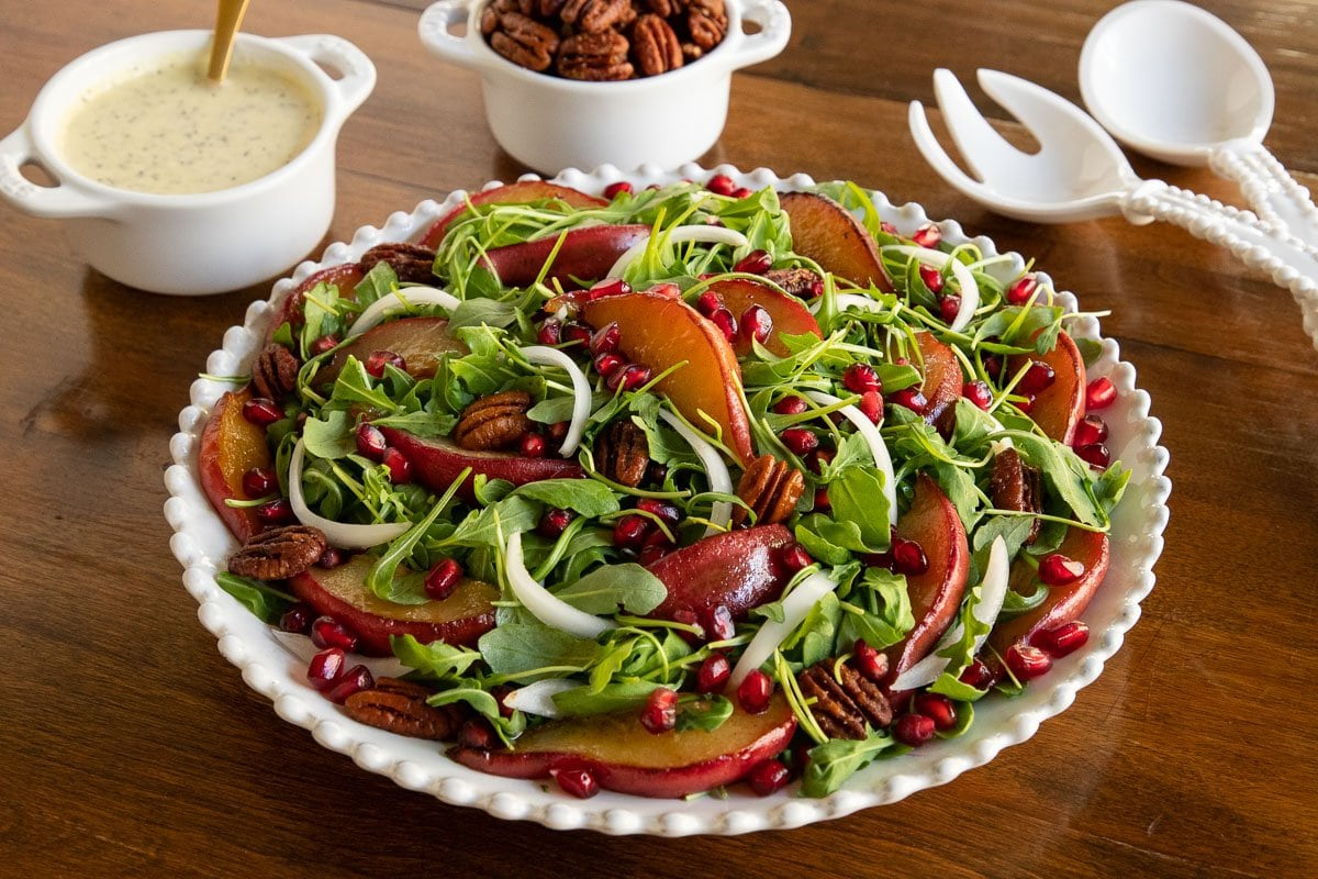 Horizontal photo of a white serving platter of Caramelized Pear Arugula Salad on a wood table.