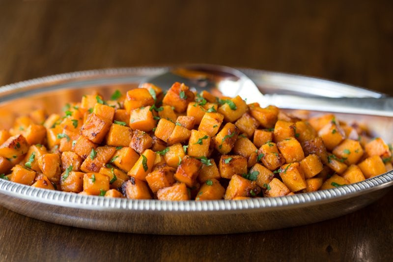 Photo of a pewter platter filled with Caramelized Sweet Potatoes and a serving spoon on a wood table.