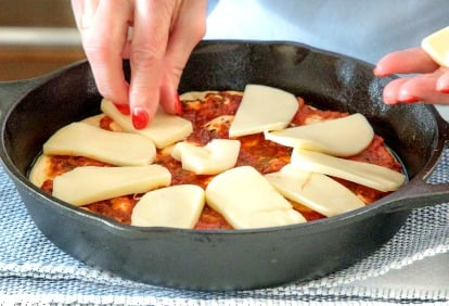 A process photo of placing mozzarella cheese slices on an Easy Deep Dish Pepperoni Pizza in a cast iron skillet.
