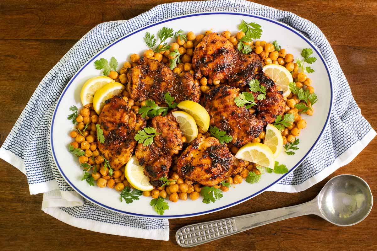 Horizontal overhead photo of Charred Honey Lemon Chicken with Crispy Chickpeas on a white serving platter resting on a wood table.