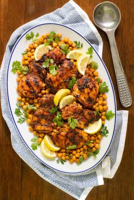 Vertical overhead photo of a platter of Charred Honey Lemon Chicken with Crispy Chickpeas on a wood table.